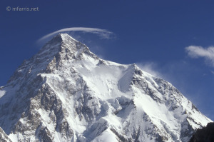 A cloud reveals the summit winds over K2
